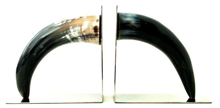 21st century pair of contemporary and sleek polished black natural horn and chrome bookend sculptures. These timeless sculptural horn bookends feature polished black and tan polished buffalo horn mounted on sleek polished chrome book ends. Each