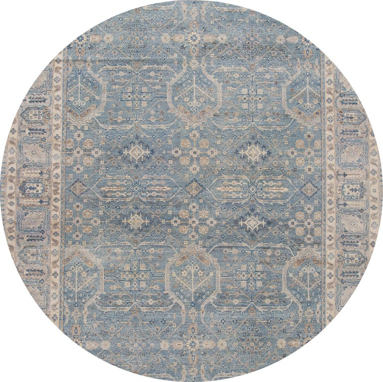 A contemporary Tabriz style rug with a tan field and ivory and blue accents in a symmetrical, interconnected floral and vine design. This hand knotted wool.