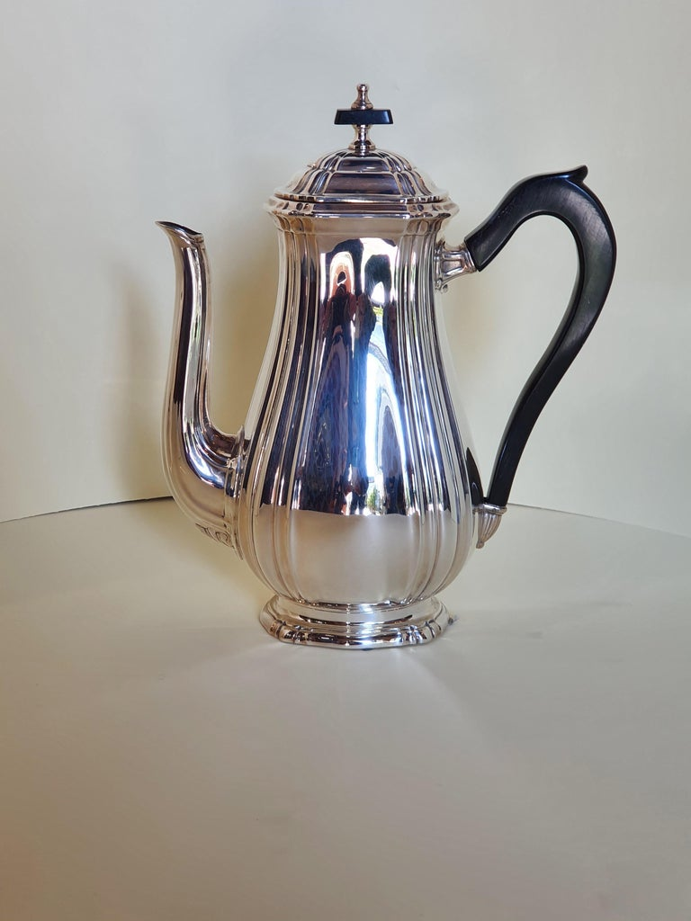 An elegant Georgian style tea and coffee set in hand chiseled sterling silver by the Italian silversmith Argenteria Auge. Composed of 4 objects: one teapot, one coffee pot, one sugar bowl with lid and a milker. Pieces are in pear-shaped form with