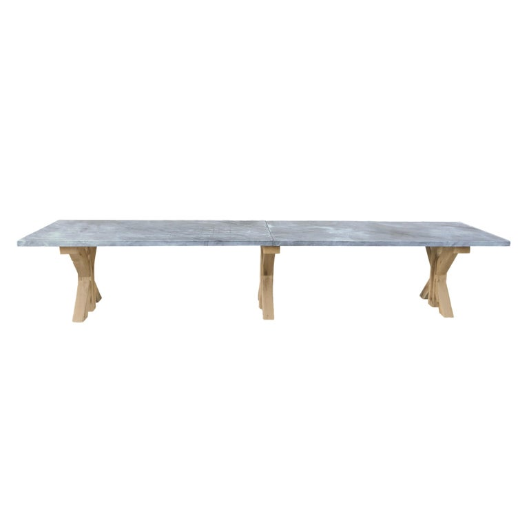 Rustic table base in oakwood with three legs and a sandblasted oversized grey marble top.