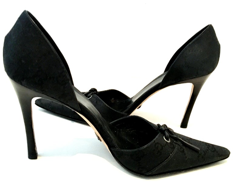 """21st Century Black GUCCI Canvas And Leather """"GG"""" Logo Stiletto Heel Shoes. canvas and leather bow shoes. Features a black canvas """"GG"""" logo body, pointy toe with leather bow detail and wood stiletto heels. Made in Italy, size: Size 8.5 B USA- 4"""