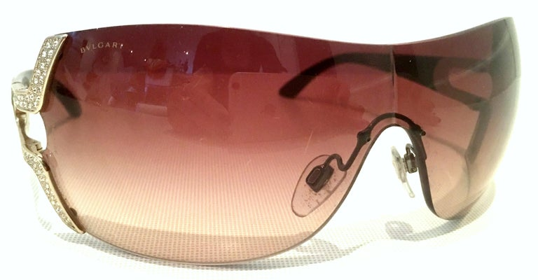21st Century Italian Silver Embellished Swarovski Crystal Bvlgari Logo Sunglasses  These silver plate, brown acetate frame with amethyst gradient lens glasses feature colorless cut and faceted brilliant pave set Swarovski crystals, with Bvlgari