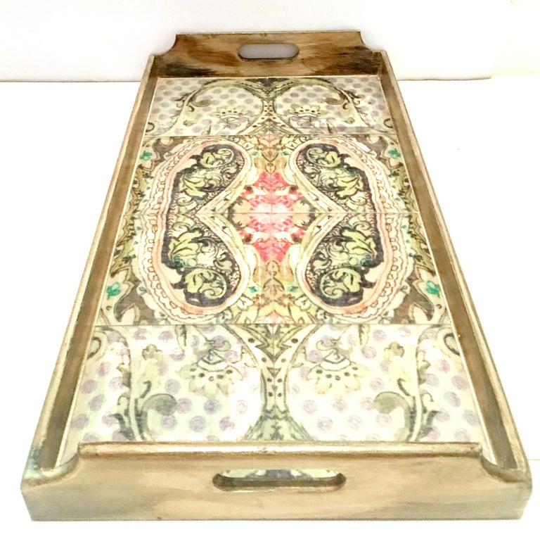 21st century and new large solid wood, printed Belgium linen and glass cut out handle tray. This faux aged solid wood tray features a printed Belgium linen in a paisley pattern under beveled and pillowed tile glass, with cutout handles.