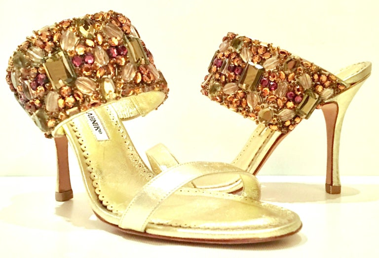 21st Century & New Pair Of Gold Metallic Leather & Swarovski Crystal Embellished Stiletto Sandal Shoes By, Manolo Blahnik. Features metallic gold leather with strap encrusted prong set Swarovski Crystal rhinestones. Original Neiman Marcus retail tag