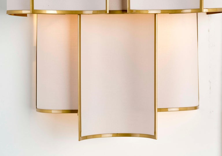 Shade Collection - A composition of small curved framed panels that create a luminous movement, also available in other finishes and fabrics, as well as sizes. All Officina Luce items are customizable.  Main structure in natural brass in satin