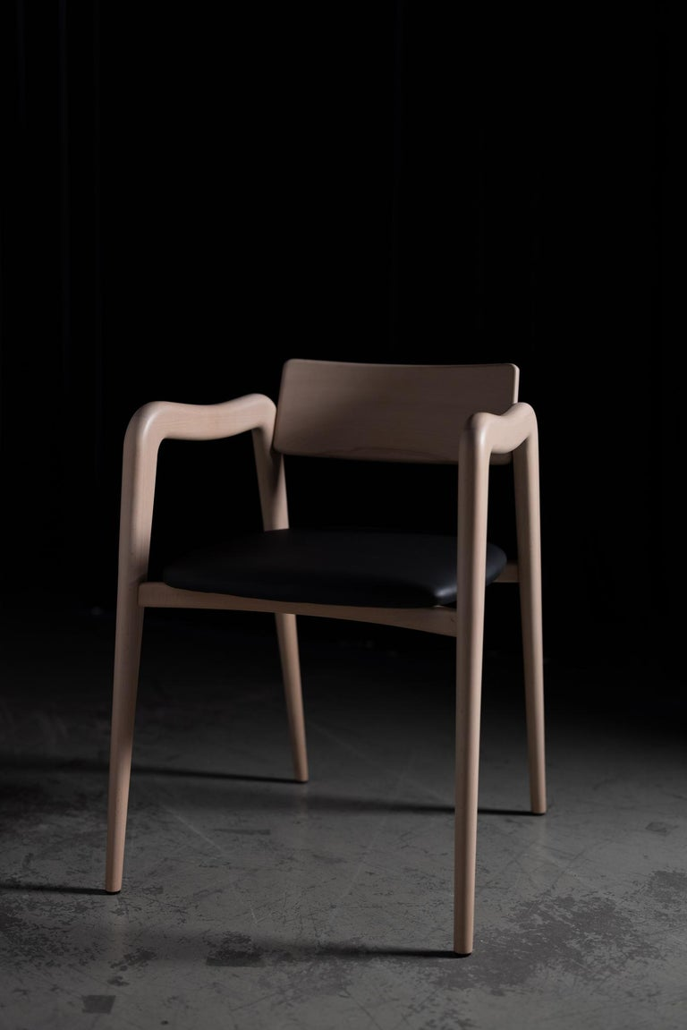 21st century contemporary modern solid beech Anjos chair with armrests black leather handcrafted in Portugal - Europe by Greenapple.   Anjos Chair Materials Solid beech chair, natural with matte finish. Seat upholstered in black high standard