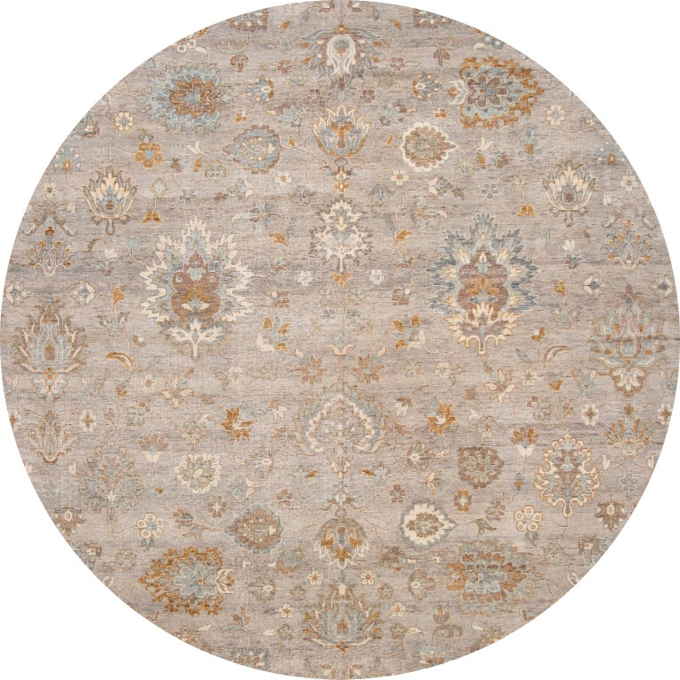 Beautiful contemporary Indian rug, hand knotted wool, with a light gray field, tan and ivory accents in an all-over Classic motif, circa 2019. This rug measures 10' X 13' 10
