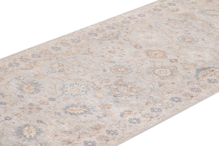 Beautiful contemporary Indian runner rug, hand knotted wool, with a light gray field, tan and blue accents in an all-over Classic motif, circa 2019. This rug measures 3' x 19' 10