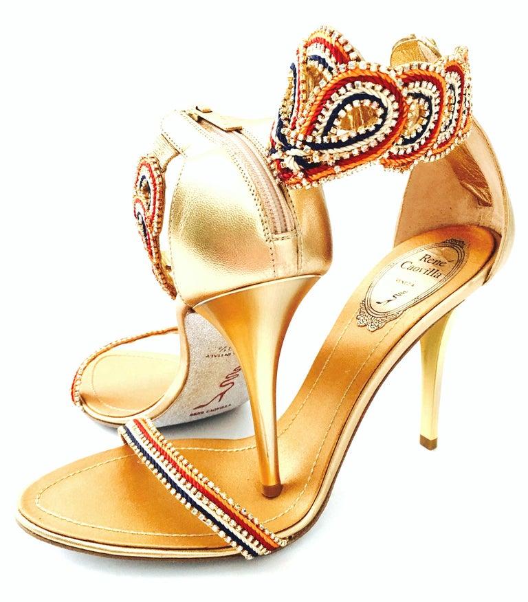Contemporary, New & Patriotic gold metallic leather Rene Caovilla sandals with multi color, red, white, blue and orange woven details. Aurora borealis Swarovski crystal rhinestone embellishments throughout. Gold metallic 4