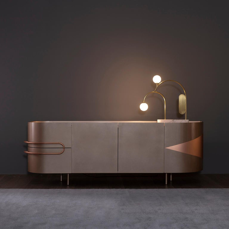 Wooden sideboard lacquered in rose gold bronze powder, high-gloss finish. Top in polished Pink Onyx. Contains drawers and shelf compartments and interior LED lighting triggered on door opening. Inlay metal details and handles in brushed copper with