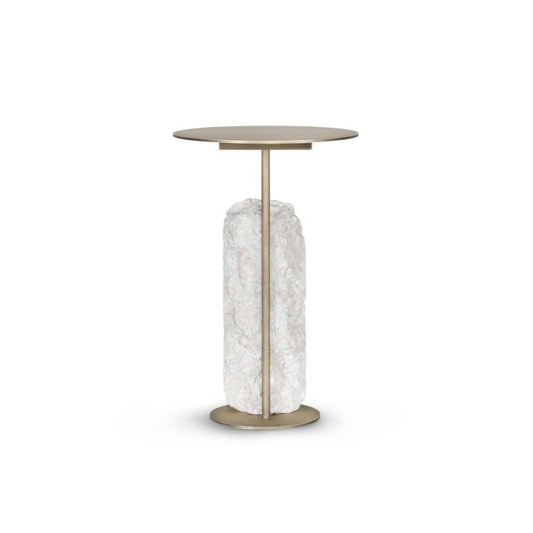 Side table in oxidised brass with matte finish. Base block in matte Grey coral stone with a split face effect.