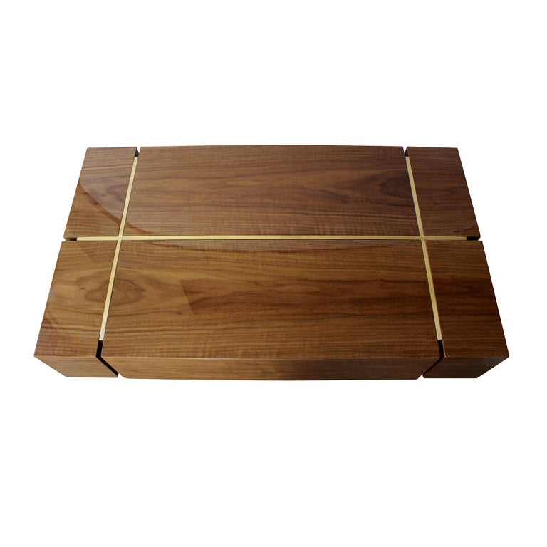 The modern center table is split into five American walnut wood structures which gives shape to the top. The base is made in brushed brass and holds the marvelous wooden top, turning this modern furniture piece into an essential addiction to any