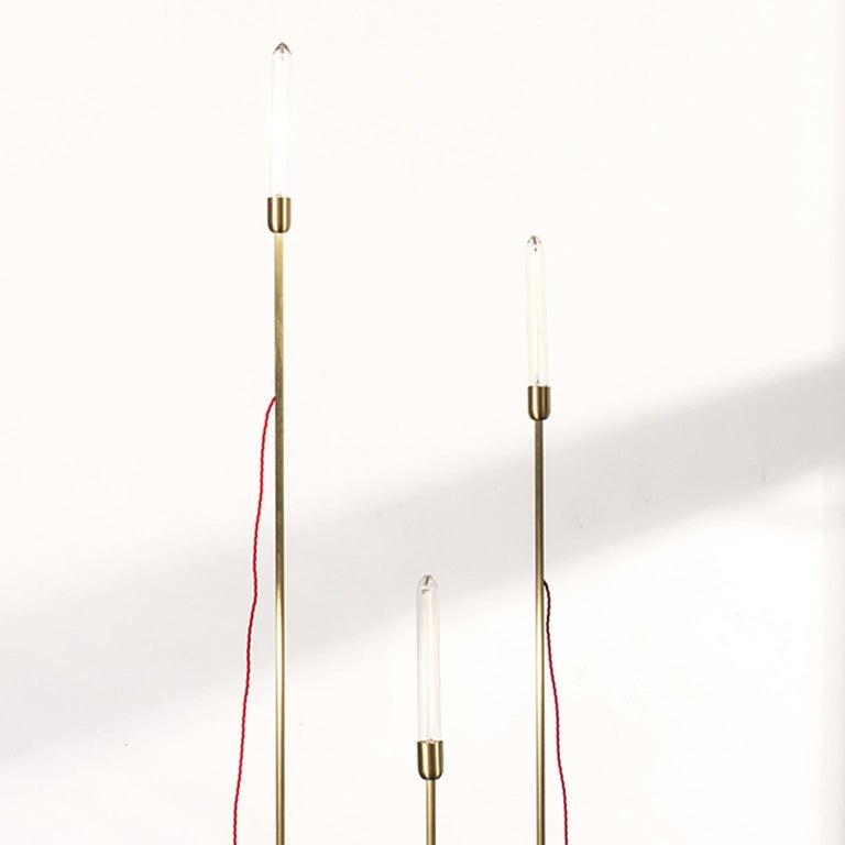 This installation is composed by a group of standing lights. The stems in opaque brass of each light have different heights, and the handmade base is in rough iron. The light bulbs are in retro stile incandescence or led. Colored fabric wires are a