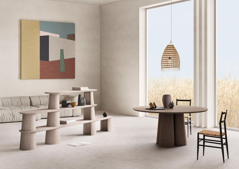 Rounded shape dining table part of a collection of modular system in ultra-high performing cement mortar. UHPC tabletop and base colored in the mixture and sandblasted. Available in eight different colors: Brick, silver, powder, cream, fir, dark,