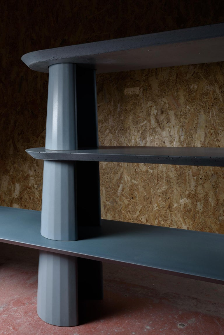 Bookcase part of a collection of modular system in ultra-high performing cement mortar. UHPC tabletop and base colored in the mixture and sandblasted. Available in eight different colors: Brick, silver, powder, cream, fir, dark, chocolate, ink and