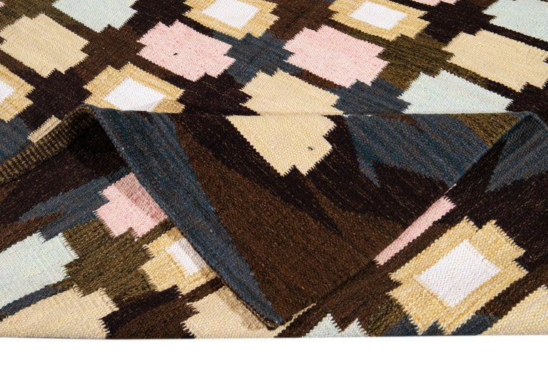 Beautiful Modern Swedish-Style with brownfield and multicolored geometric patterns all over the rug.   This rug measures 8' 3