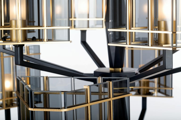 Top Glass collection, a sophisticated line where the matte black finish designs geometries on the solid faceted structure and the shades are composed of glass elements in golden cages.   Shades in transparent glass elements in fumè color, central