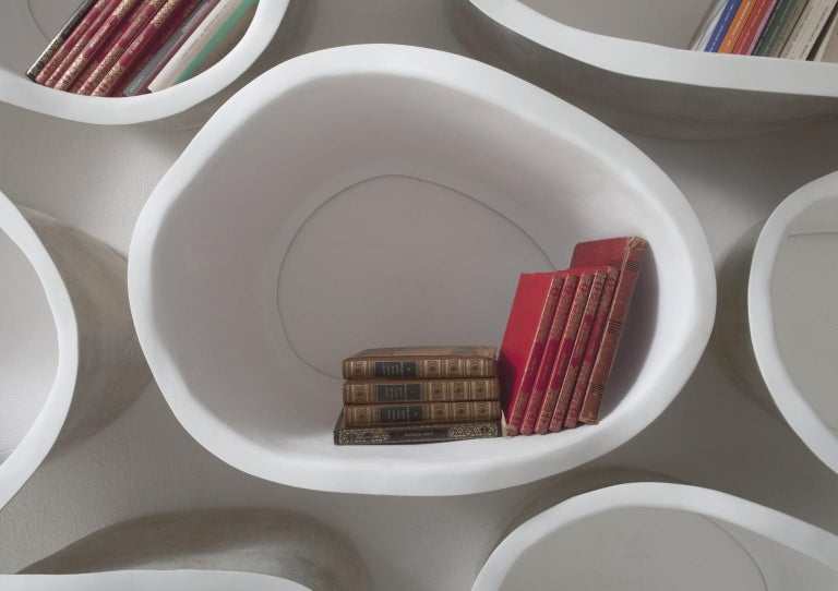 Favo bookshelves and containers, modular wall elements in fibreglass.  The individual modules can be juxtaposed, turned around and multiple, 2 elements but various combinations of shapes. Favo positioned in a seemingly casual pattern allows
