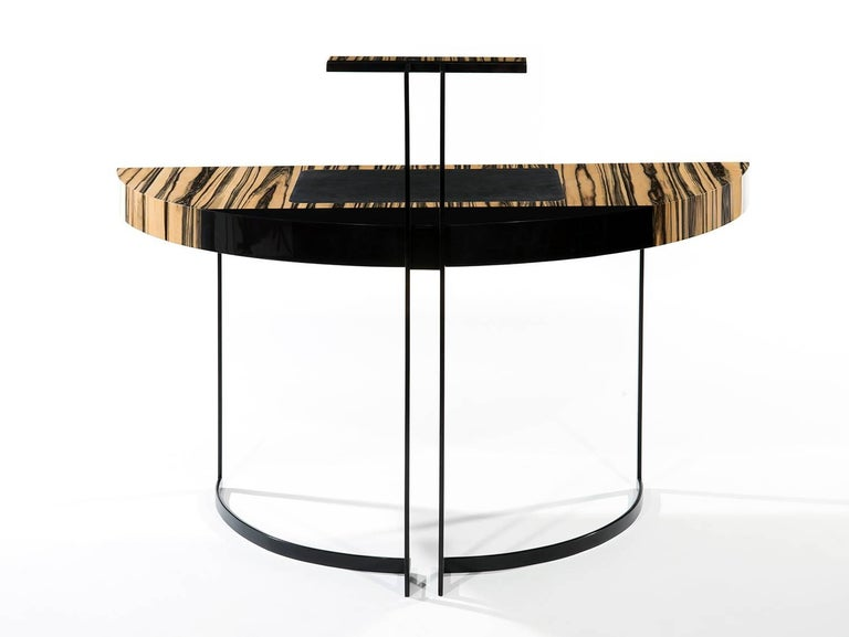 A semi-circular black lacquered metal legged desk with a white ebony veneer top and black leather desk blotter. The top of the back legs ends with a LED light.  Information about the covid 19.  At this point, the workshop has anticipated the crises