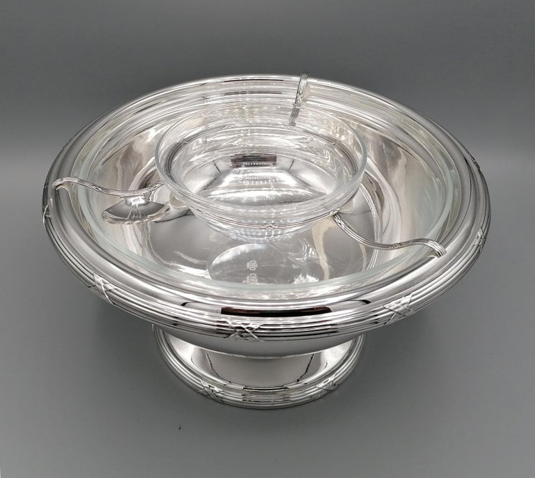 Important bowl for caviar by Gianmaria Buccellati. The body was made in two parts, cup and base. The welded edge with cross ribbon characterizes the Classic Luis XVI style. A wire circle, also in silver, supports a crystal cup for caviar, while a