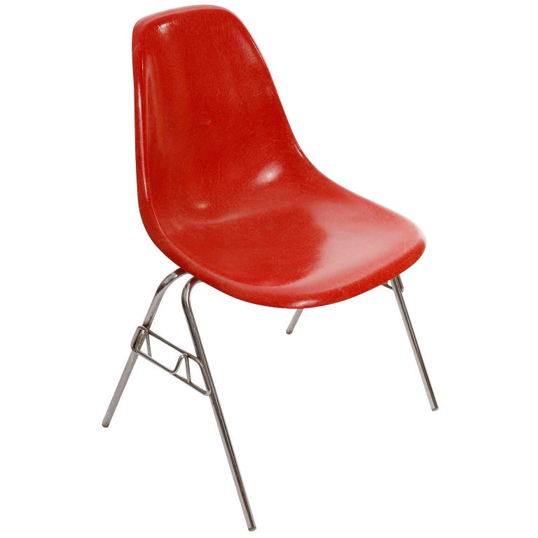 One of 22 stackable dining room chairs by Charles & Ray Eames for Herman Miller, manufactured in midcentury, 1974. The chairs are labeled on the underside of the seats with 'herman miller' and stamped with 28. Nov. 1974. A molded red fiberglass