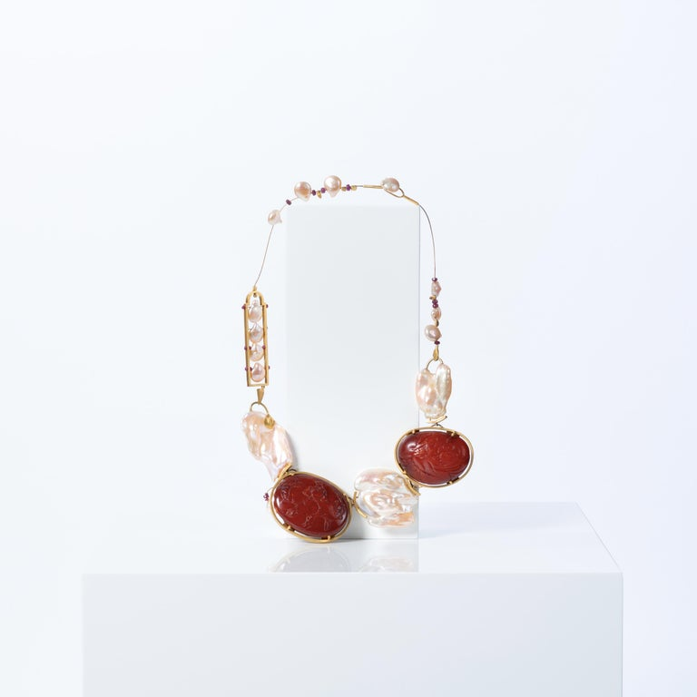Artist and architect Daniel Azaro was asked by Mimi Lipton to craft this one-of-a-kind necklace. Timeless and bold, the jewel is adorned with rubies, Baroque pearls and Baltic amber pieces set in 22 karat gold. The amber was carved in China in the
