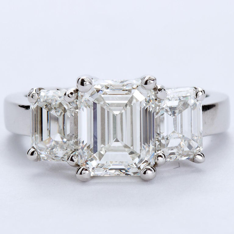 A very fine three stone ring set with a GIA certified center 2.20 ct H color VVS1 clarity Emerald cut diamond and two side stones, 1.01 carat each H color VVS1 clarity. Total diamond weight 4.22 ctw. Stones are set in a four prong three stone