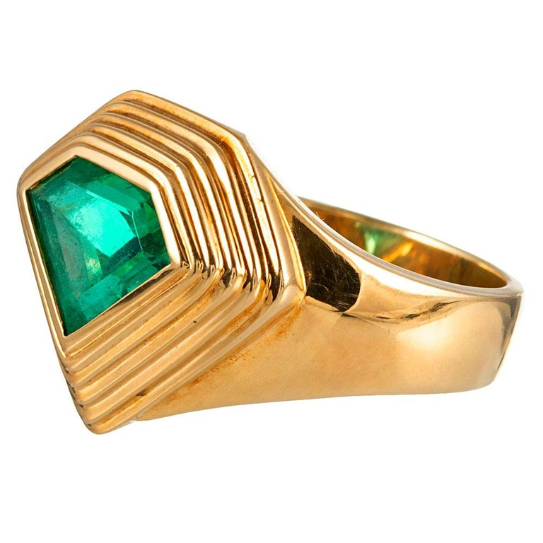 An unusually-shaped emerald of 2.20 carats sits nestled in a tiered bezel of 18 karat yellow gold. The mounting both enrobes the stone in golden light and protects this delicate gemstone from harm, allowing it be worn daily. The band tapers down the