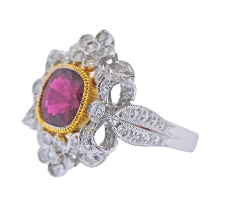 18k white and yellow gold ring with a center approx. 2.20ct ruby (measuring 8 x 7.6 x 4.1mm), surrounded with approx. 0.76ctw in diamonds. Ring size - 6.75, ring top - 21mm x 22mm. Marked 750. Weight - 7.9 grams.