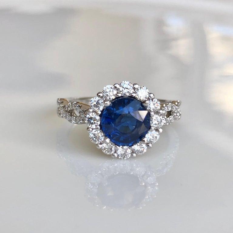 2.20 Carat Sapphire Diamond Halo Engagement Ring 18K White Gold  Primary Stone: Natural Sapphire Sapphire  Weight: 1.51 Carats (6.9mm diameter)  Shape or Cut Sapphire: Round Average Color & Clarity Sapphire: Fine Sapphire Vivid Blue /VS  Accent