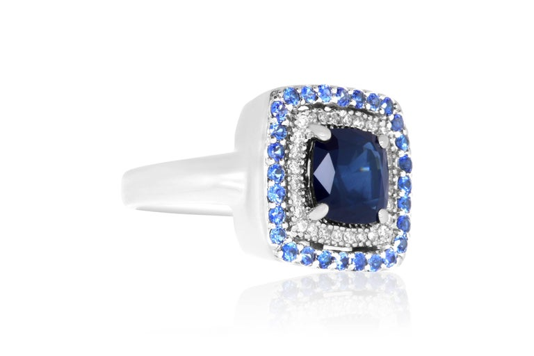 Material: 14k White Gold  Center Stone Details: 1 Cushion Cut Blue Sapphire at 2.25 Carats - 7mm Mounting Details: Brilliant Round White Diamonds at 0.10 Carats. Clarity: SI / Color: H-I.  28 Round Blue Sapphires at 1.20 Carats. Ring Size: Size 5.25
