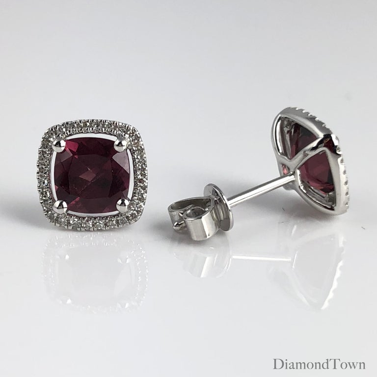 These stunning halo stud earrings feature 2.27 carats Raspberry Garnet, surrounded by a halo of round white diamonds.  Center: two cushion cut Garnet stones total 2.27 carats Diamond Halo: 56 round diamonds total 0.16 carats Set in 14k White
