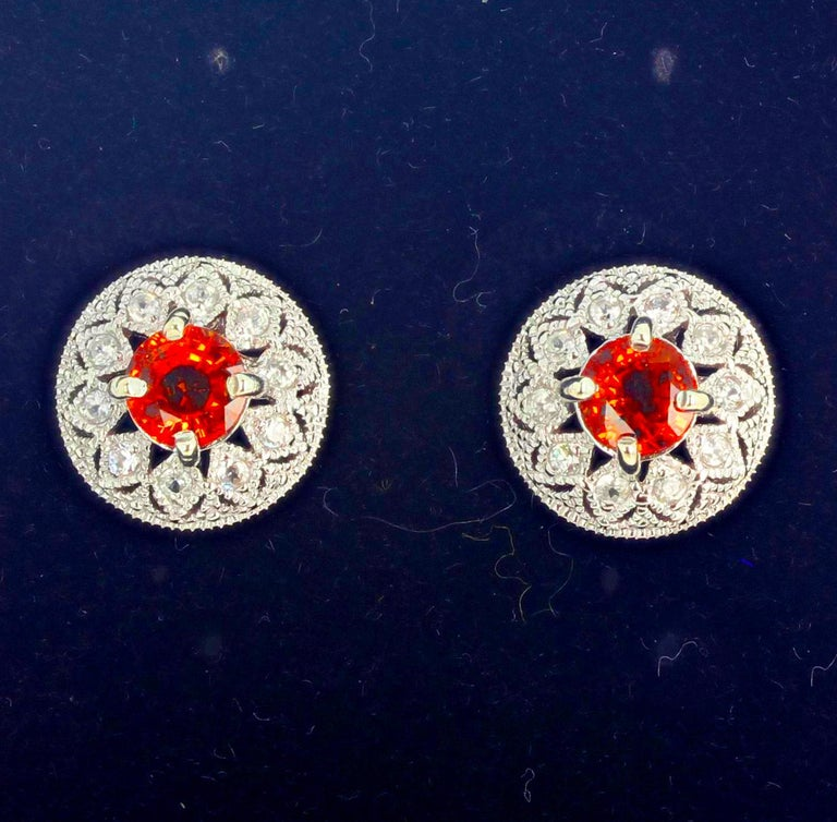 These brilliant orangy red glittering Songea Sapphires ((6mm) are set with accents of brilliant teeny tiny Diamonds in white gold rhodium plated sterling silver stud earrings.  The earrings are approximately 13 mm in diameter.  More from this