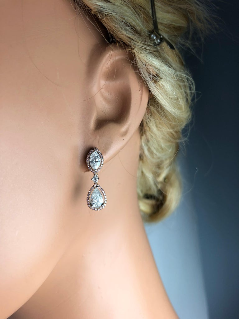 These gorgeous stud drop dangle earrings each feature a marquise cut and a pear shape diamond, linked by a smaller round diamond. The center stones are encircled by halos of round pink diamonds.  Two Pear shape diamonds are 1.01 carats. Two Marquise