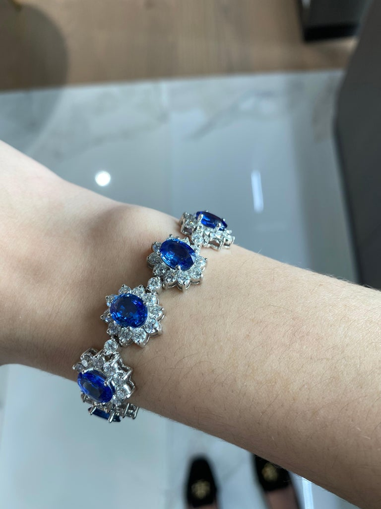 This absolutely exquisite bracelet features a whopping 22.96ct total weight in 11 oval shaped, richly saturated, blue natural sapphires, surrounded by round diamond halos forming a floral shape. The round diamonds add up to a total weight of