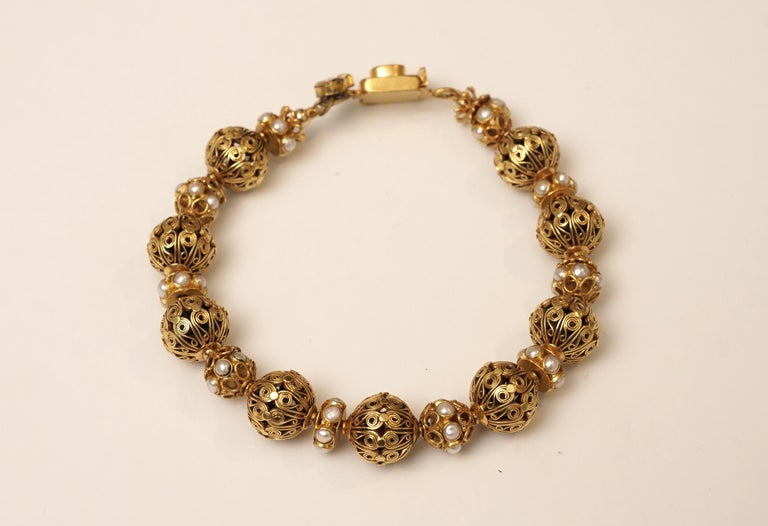 22k gold bead bracelet with intricate and beautiful wire work and pearl and gold rondelles in between.  A sapphire push clasp with rose cut diamonds.  8.5 inches long.