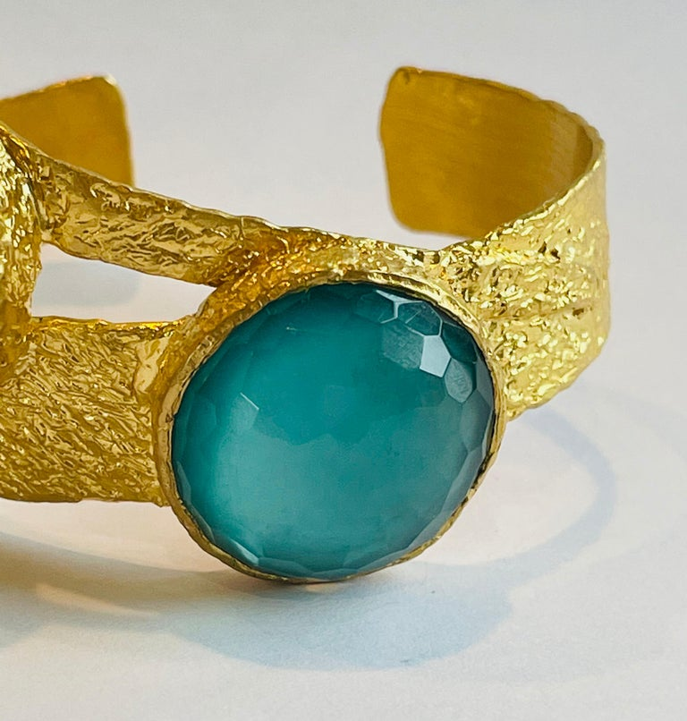 22k gold cuff featuring 2 beautiful sliced stones both with Quartz on top and one with Turquoise and other with Mother of Pearl on the bottom. The combinations of these stones together results in absolutely beautiful pop of color and a completely