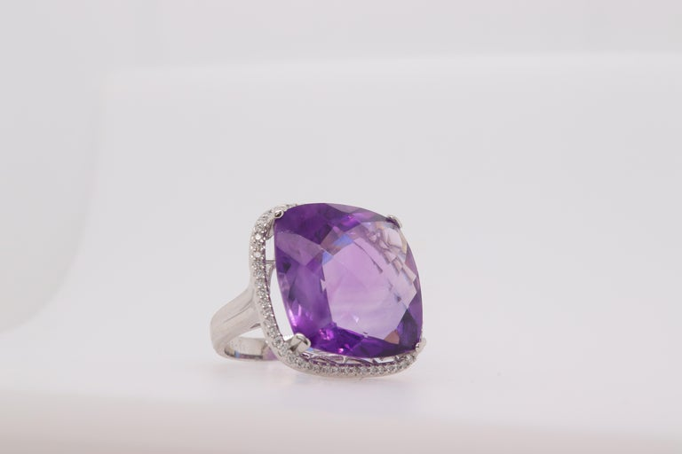 A uniquely large purple amethyst cocktail ring.  Material: 14k White Gold  Stone Details: 1 Cushion Amethyst at 23.25 Carats Measuring at 19mm Mounting Stone Details: 60 Brilliant Round Diamonds at 0.38 Carats Ring Size: 6.5. Alberto offers