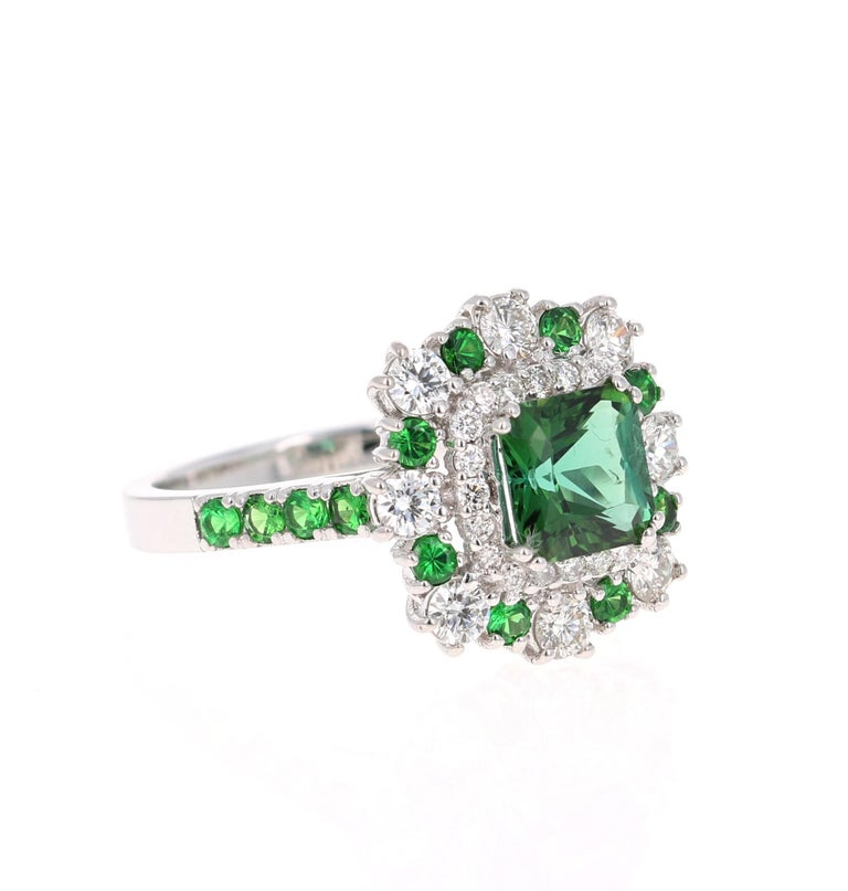 This gorgeous ring has a beautiful Square Cushion Cut Tsavorite weighing 1.36 carats and is surrounded by 27 Round Cut Diamonds weighing 0.70 carats and 8 Tsavorites that weigh 0.27 carats. The total carat weight is 2.33 carats.    It is set in 18K