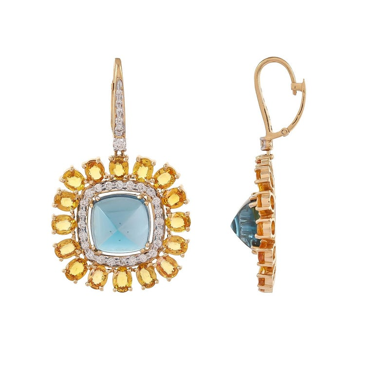 The cushion-shaped sugar loaf blue topaz weighing approximately 23.31 carats, within a frame of 16 oval-shaped yellow sapphires weighing approximately 14.06 carats, decorated with 1.31 carats diamonds and mounted in 18 karats yellow gold. stone