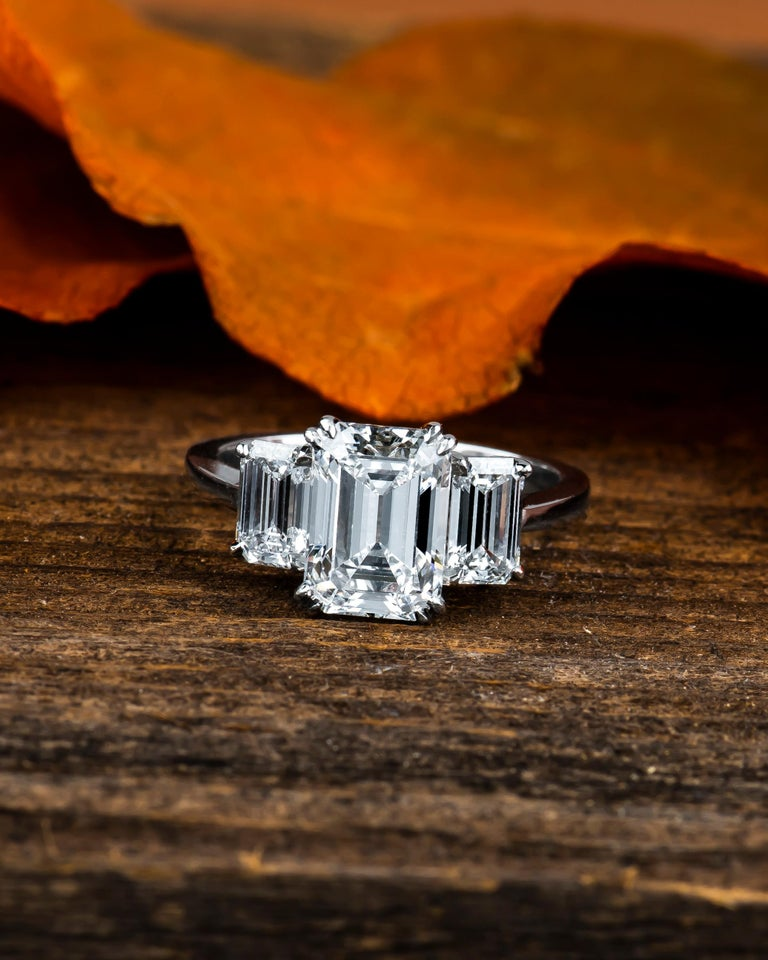 2.36 Carat D VVS2 (GIA report) emerald cut diamond with 1.02 carat total weight in side diamonds, D-E color, VS2 or finer clarity (non-certified). Platinum 3 stone ring, size 5.5,  size can be adjusted larger or smaller upon request.