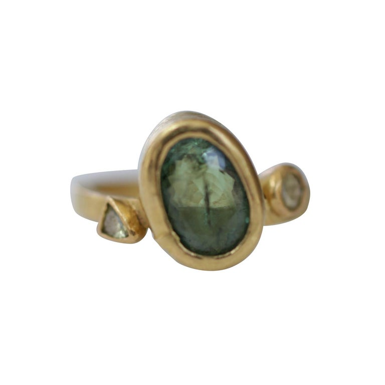 Our Popcorn Garnet Ring delivers a rich pop of green color. Whimsical bridal or stackable fashion three-stone ring in recycled 22k textured gold, featuring green Russian demantoid garnet flanked on both sides by two yellow rose cut diamonds. The