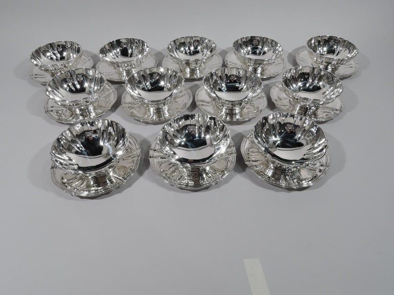 Serve dessert for 12 with this beautiful set of sterling silver bowls and plates. Made by Tiffany & Co. in New York, circa 1911. This set comprises 12 bowls and 12 plates. Each bowl: Curved and fluted sides, reeded rim, and stepped foot. Each plate: