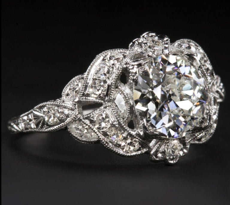 This stunning Art Deco engagement ring features a phenomenally brilliant, beautifully white, and completely eye clean old European cut diamond complemented by a richly detailed diamond encrusted platinum setting. Cut by hand during the 1920s-1930s,