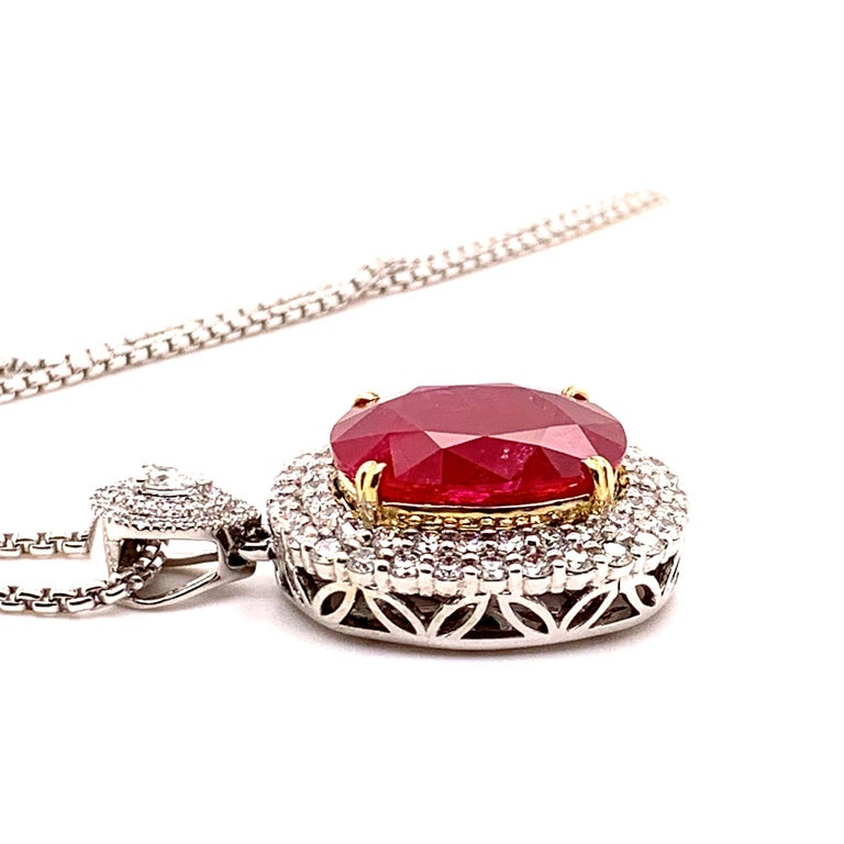 Glamorous large ruby diamond pendant necklace. Intense fiery red, high luster, cushion faceted, 24.21 carats natural ruby mounted in high profile with yellow gold eight knife prongs, accented with two rows of round brilliant cut diamonds, bail with