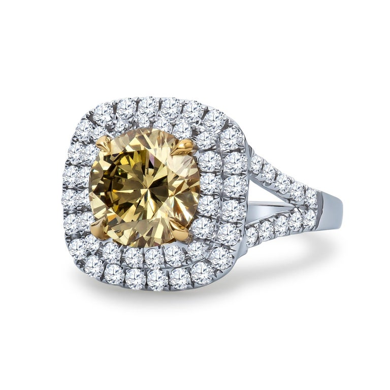 2.43 Carat, GIA certified, round brilliant cut 'natural fancy brownish greenish yellow' center diamond with a VS2 clarity. Double halo form in 0.94 carats total weight in accent diamonds set in an 18K white and yellow gold ring with filigree detail.