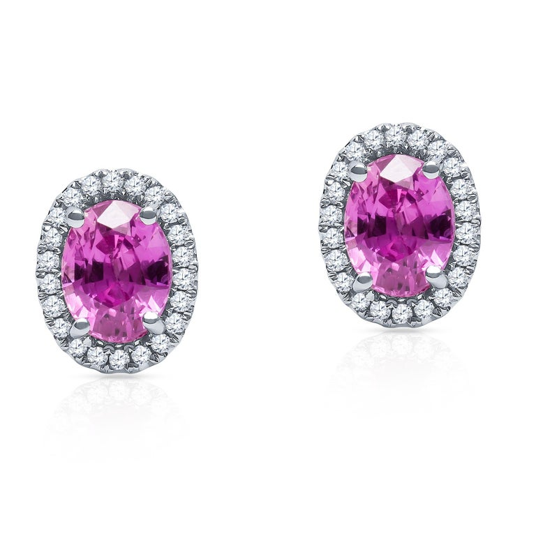 2.44 carat total weight oval natural pink sapphires with 0.17 carats total weight in round brilliant diamond halos.   Diamond quality: G-H color, SI1 clarity