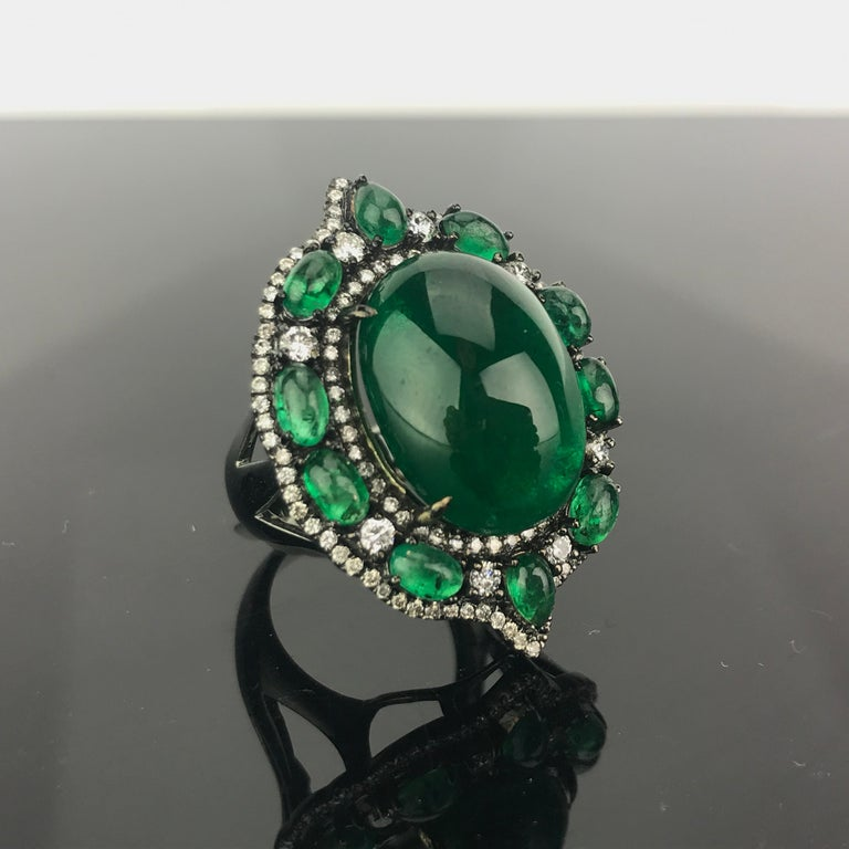 A beautiful, transparent Oval Cabochon Zambian Emerald, adorned by smaller Emerald Cabochons and Diamonds all set in 18K Gold, rhodium plated. Can provide certificate upon request.  Currently sized at US 6, but we can change the ring size without