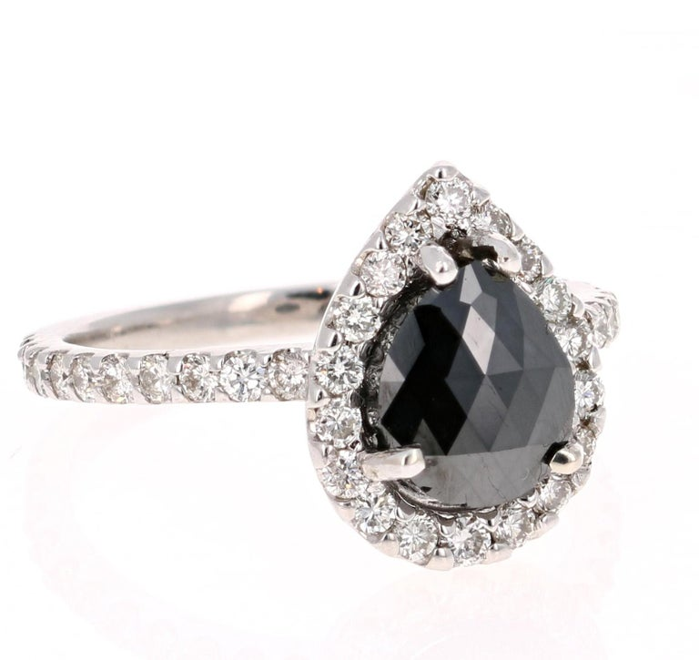 A stunner that can transcend into a unique engagement ring!! This ring is made in 14K White Gold and weighs approximately 3.5 grams.   The Black Diamond is a Pear Cut and weighs 1.77 carats. The Black Diamond is a natural diamond that has been