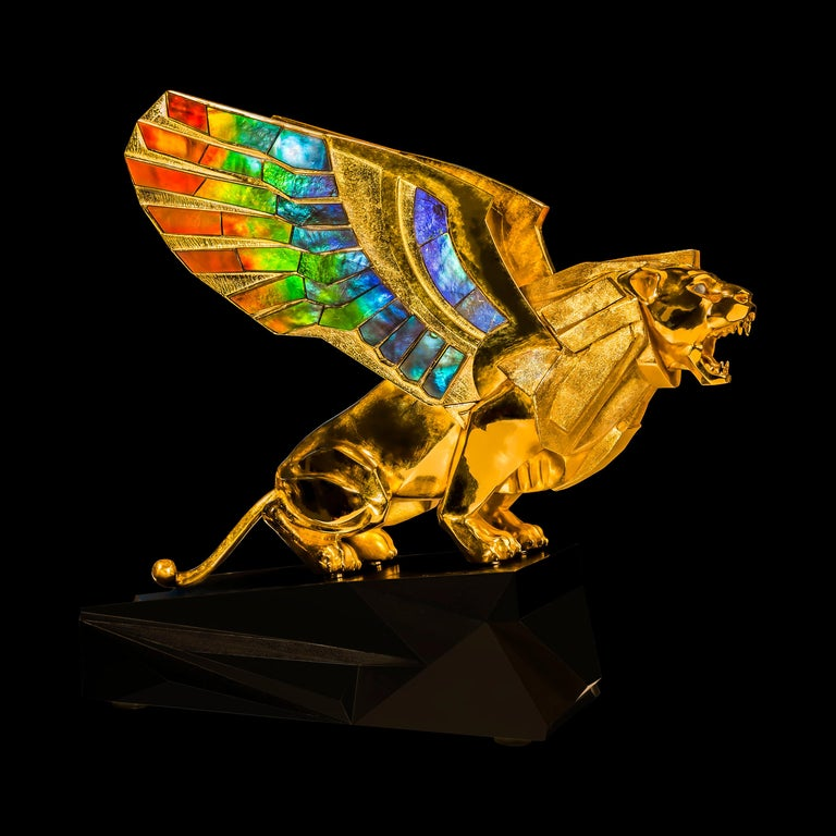 Golden gryphon sculpture in 24K gold plated sterling silver, with wings set with AAA grade ammolite, chrysoberyl cat's eye set upon an oxidized bronze pedestal.  The sculpture depicts a mighty Gryphon crouching in tension is prepared to jump. Its